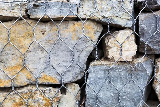 Rotsen en steen met metalen hek