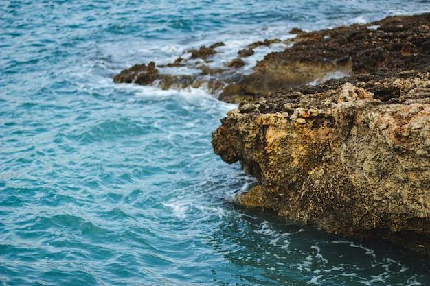 Rotsen en stenen op het strand, overdag omgeven door water