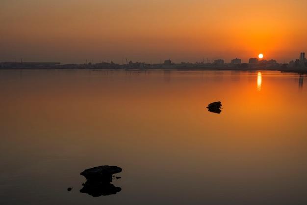 Rotsen met bezinningen over kalm water en mooie zonsopgang over kleurrijke hemel met silhouetachtergrond, bahrein.
