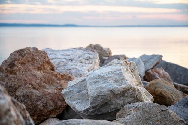 Rotsen op de egeïsche zeekust bij zonsondergang, land in de verte in skala fourkas, griekenland