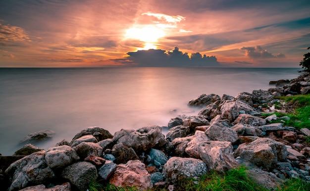 Rotsen op steenstrand bij zonsondergang