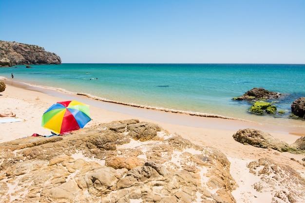 Rotsen op zandig praia do amado-strand, portugal