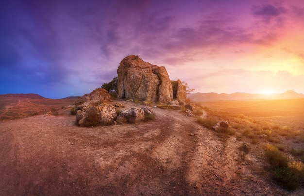 Rotsen tegen verbazende bewolkte hemel in woestijn bij zonsondergang