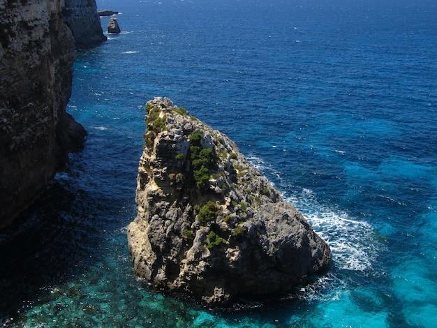 Rotsen van de kustlijn van comino in malta omgeven door water