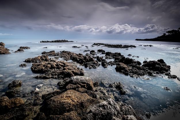 Rotsformaties in de zee onder de bewolkte hemel