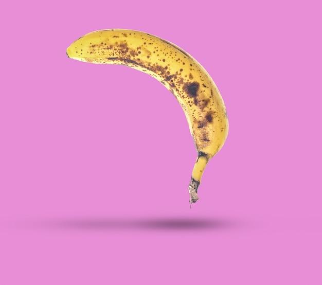 Rotte banaan met zwarte vlekken geïsoleerd op paarse tafel