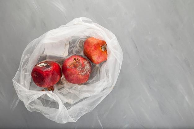 Rotte bedorven granaatappel met schimmel in wegwerp plastic zak