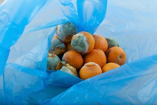 Rottende mandarijnen in blauwe plastic zak