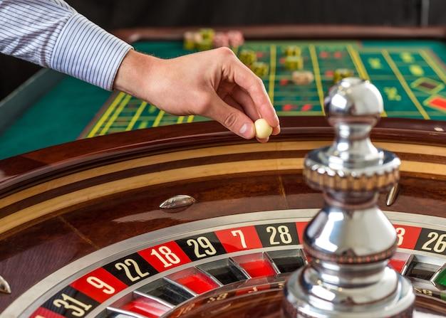 Roulettewiel en croupierhand met witte bal in casino