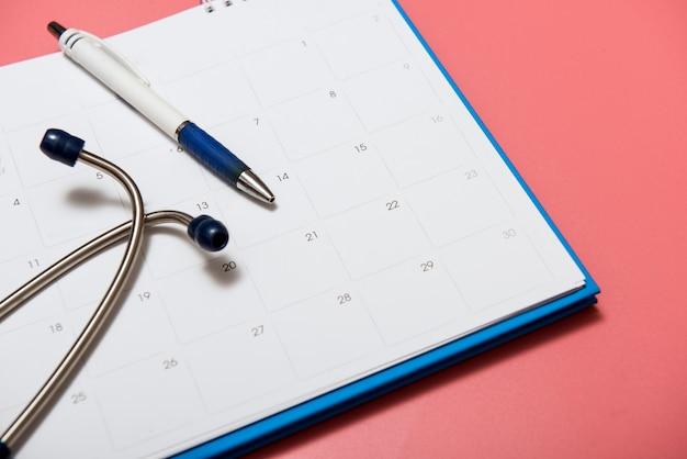 Routine medisch examen vertegenwoordigd door een deel van stethoscoop, kalender en pen.
