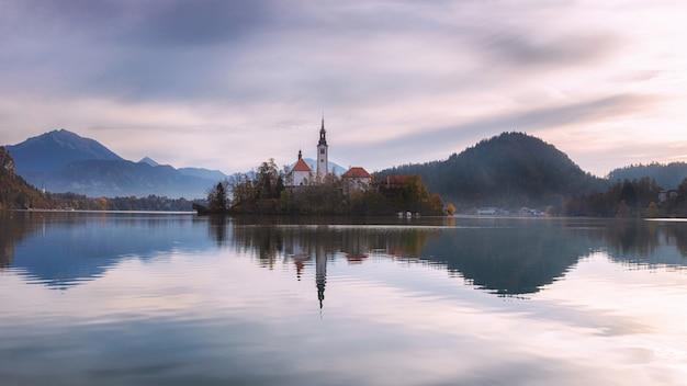 Rouw weergave van lake bled met een paarse bewolkte hemel, slovenië