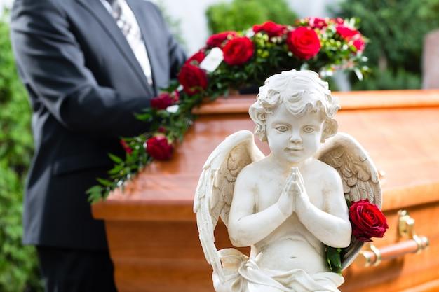 Rouwende man bij begrafenis met doodskist