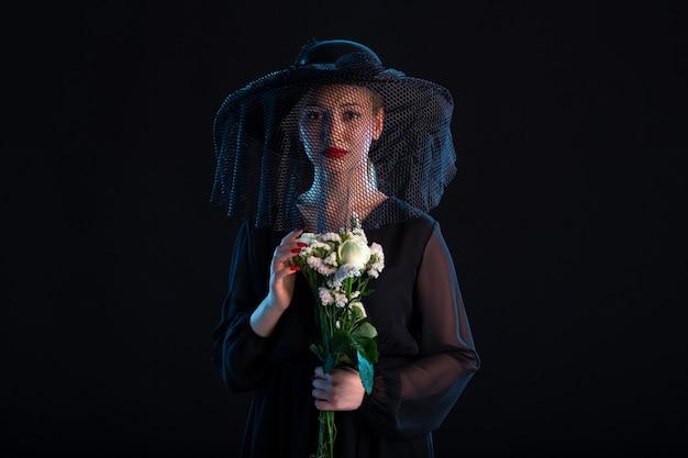 Rouwende vrouw gekleed in het zwart met bloemen op zwarte dood begrafenis verdriet