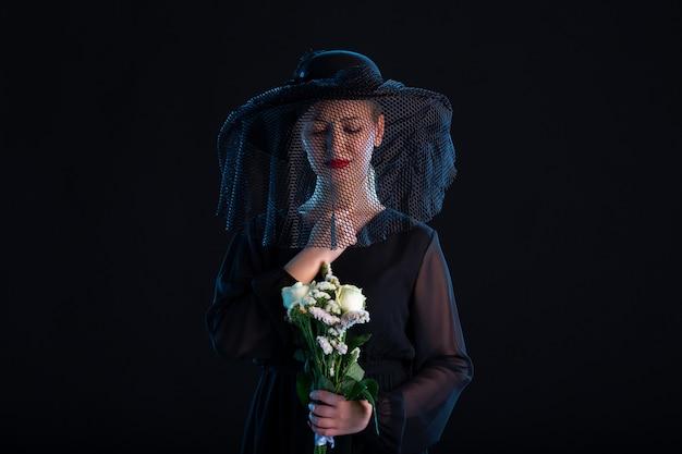 Rouwende vrouw helemaal in het zwart gekleed met bloemen op de zwarte droefheid begrafenis dood