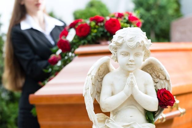 Rouwende vrouw op begrafenis met rode roos die zich bij kist of kist bevindt