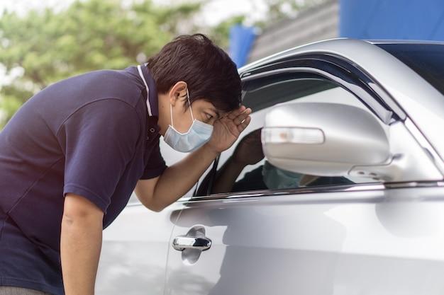 Rover en de autodief in een masker openen de deur van de auto en kapen de auto.
