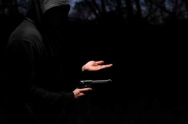 Rover met een pistool 's nachts. gevaarlijke crimineel. man in hoodie die overvalt voor geld.