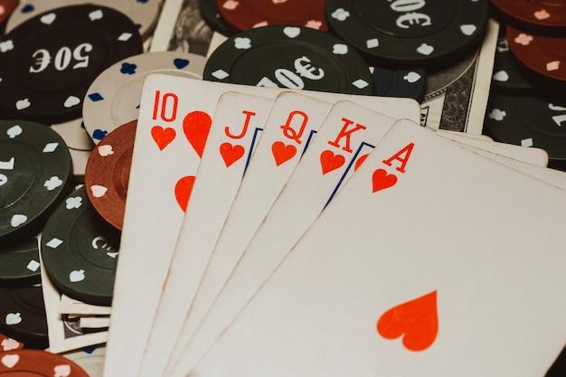 Royal flush in poker op de achtergrond van spelchips en gelddollars
