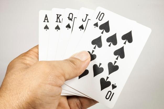Royal flush speelkaarten in de hand op witte achtergrond