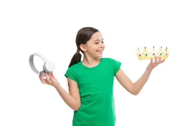 Royalty-vrije muziek. pop prinses. koningin van de muziek. portret van vrolijk meisje geïsoleerd op wit. gelukkige jeugd. klein meisje kiezen tussen kroon en koptelefoon. een superster zijn. beste hitlijst.
