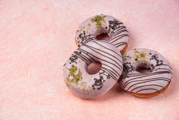 Roze aardbei donuts geïsoleerd op roze achtergrond.