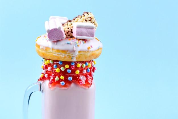 Roze aardbei freakshake met marshmallow en snoep.