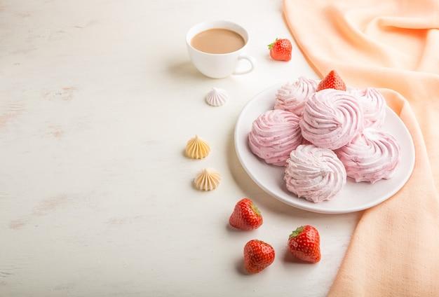 Roze aardbei zelfgemaakte zephyr of marshmallow met kopje koffie op witte houten oppervlak met oranje textiel