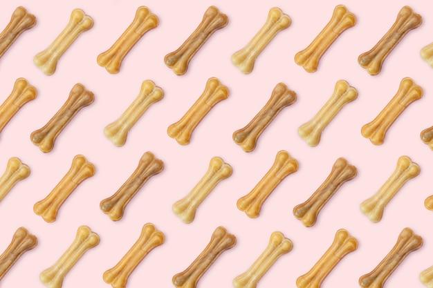 Roze achtergrond van veel hondenspulletjes in de vorm van een bot