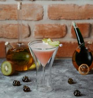 Roze alcohol vanillecocktail in een kosmopolitisch martini-glas.