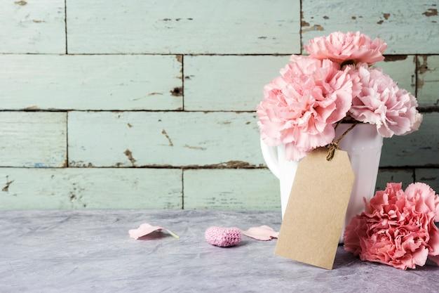 Roze anjerbloem in witte kop met lege pakpapiermarkering en hart