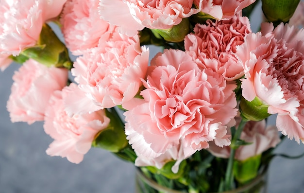 Roze anjerbloemen in glasvaas
