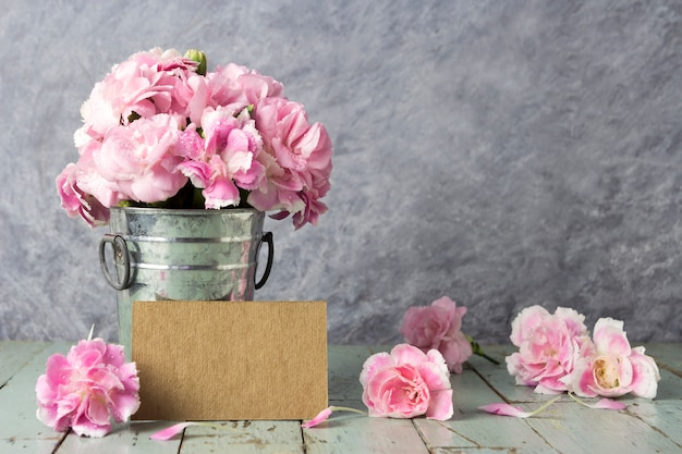 Roze anjerbloemen in zinken emmer en lege bruine kaart op oud hout