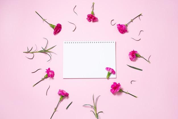 Roze anjerbloemen met open notitieboekje op roze achtergrond.
