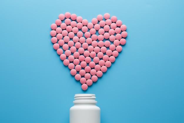 Roze b12-pillen in de vorm van een hart op een blauwe achtergrond