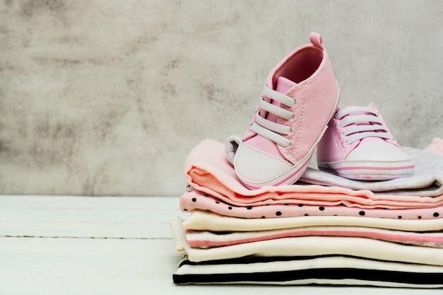Roze baby meisje schoenen en pasgeboren kleding. moederschap, onderwijs of zwangerschap concept met kopie ruimte.