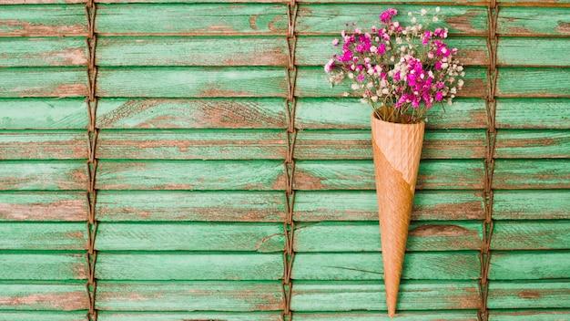 Roze babyblaadjes bloeien in de wafelkegel tegen houten luiken
