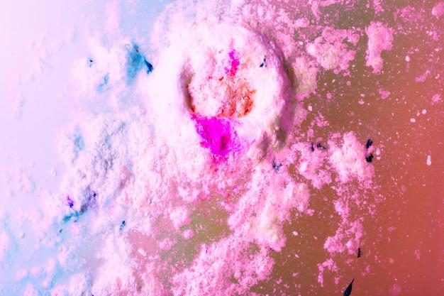 Roze badbom die op schuimbadwater drijft