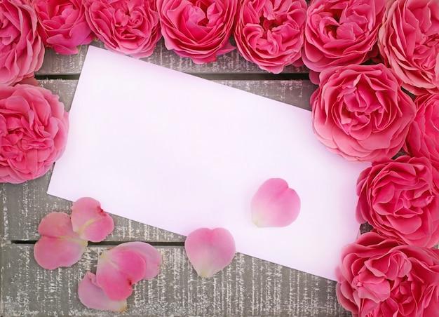 Roze badstofroos en bloemblaadjes op houten grijs