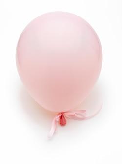 Roze ballon met fijne witte strikjes. geïsoleerd op witte achtergrond.
