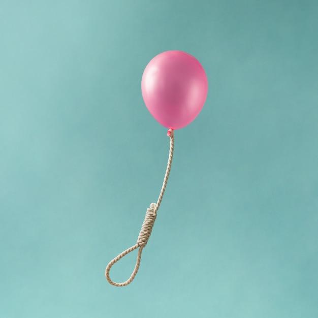 Roze ballon met strop beul op blauwe ondergrond