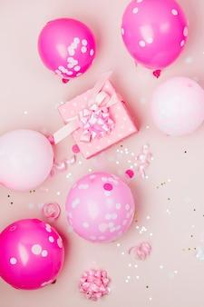 Roze ballonnen, cadeau met confetti, strikken en papieren versieringen. verjaardagsfeestje concept thema. platliggend, bovenaanzicht