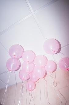 Roze ballonnen drijvend op het plafond van een feestje