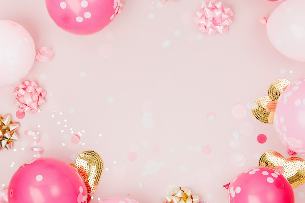 Roze ballonnen met confetti, strikken en papieren versieringen. verjaardagsfeestje concept thema. platliggend, bovenaanzicht