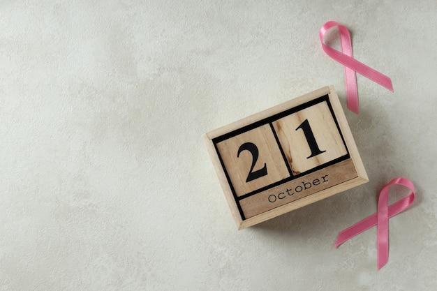 Roze bewustzijnslinten en houten kalender met 21 oktober op witte gestructureerde achtergrond