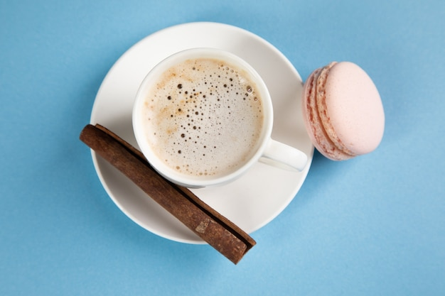 Roze bitterkoekjes en koffie met kaneel op een oranje ondergrond