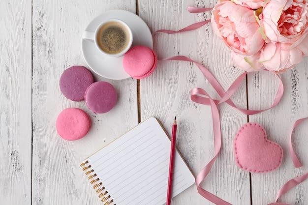 Roze bitterkoekjes met koffiekopje op houten tafel. plat liggen