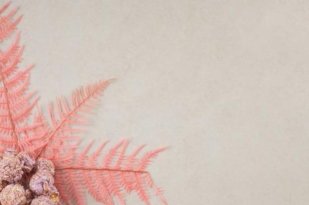 Roze bladeren die een hoopje popcornsnoepjes op marmer sieren.
