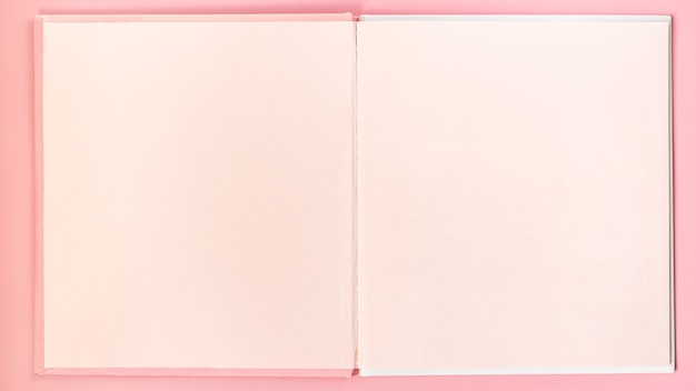 Roze blanco pagina's schetsboek op roze tafel