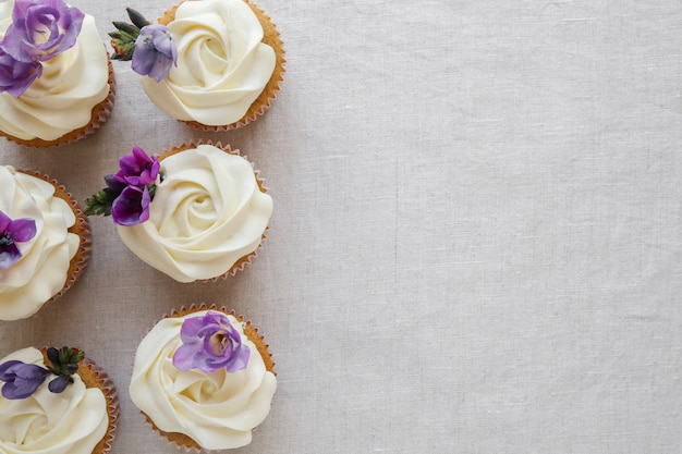 Roze bloem glazuur vanille cupcakes met paarse eetbare bloemen