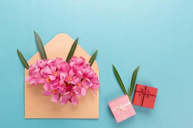Roze bloem in de envelop met geschenkdoos op blauwe achtergrond.
